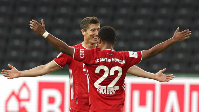 Bayern's Robert Lewandowski, left, celebrates after scoring his side's third goal with teammate Serge Gnabry during the German soccer cup (DFB Pokal) final match between Bayer 04 Leverkusen and FC Bayern Munich in Berlin, Germany, Saturday, July 4, 2020. (AP Photo/Michael Sohn)