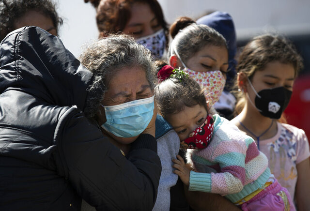 Relatives bury Isaac Nolasco who died of reasons not believed related to COVID-19, in a section of the municipal cemetery Valle de Chalco amid the new coronavirus pandemic, on the outskirts of Mexico City, Sunday, Oct. 25, 2020. Mexican families traditionally flock to local cemeteries to honor their dead relatives as part of the