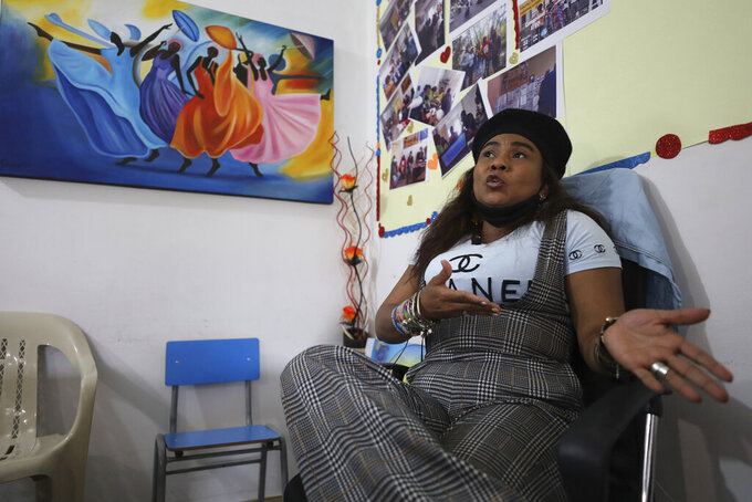 Community leader Luz Nelly Santana, whose life has been threatened by illegal armed groups, talks during an interview in Bogota, Colombia, Thursday, Dec. 17, 2020. Santana and her daughter survived a massacre where 35 people were killed during a street party and decided to flee to the capital where she has lived ever since. (AP Photo/Fernando Vergara)