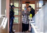 Police talk to a woman at housing commission apartments under lockdown in Melbourne, Australia, on Monday, July 6, 2020. The leader of Australia's most populous state says her government's decision to close its border with hard-hit Victoria state marks a new phase in the country's coronavirus pandemic.(AP Photo/Andy Brownbill)