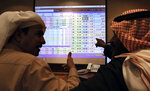 FILE - In this Dec. 12, 2019 file photo, Saudi traders chat as they follow a screen displaying Saudi stock market values, at the Arab National Bank in Riyadh, Saudi Arabia, Dec. 12, 2019. The International Monetary Fund is warning that energy-rich Gulf Arab states could burn through all their savings in the next 15 years. An IMF report released Thursday, Feb. 6, 2020, points to worries about climate change and supply from new competitors as dampening global oil prices. The IMF said those nations need to cut costs and diversify their economies. (AP Photo/Amr Nabil, File)