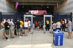 Spectators enter through the third base gate before the continuation of a suspended baseball game between the Washington Nationals and the San Diego Padres, Sunday, July 18, 2021, in Washington. The game was suspended in the sixth inning Saturday night after a shooting outside Nationals Park.  (AP Photo/Nick Wass)