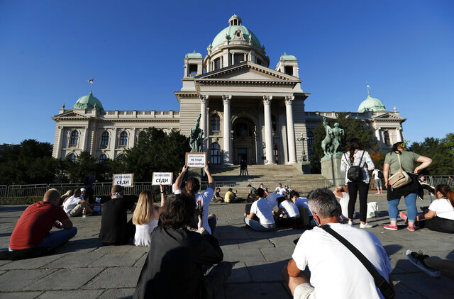 People sit during a protest in front Serbian Parliament building in Belgrade, Serbia,Thursday, July 9, 2020. Serbia's authorities on Thursday banned gatherings of more than 10 people in the capital Belgrade after two nights of violent clashes between police and thousands of demonstrators protesting coronavirus lockdown measures. (AP Photo/Darko Vojinovic)