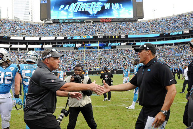 Jacksonville Jaguars head coach Doug Marrone, left, and Carolina Panthers head coach Ron Rivera speak following an NFL football game in Charlotte, N.C., Sunday, Oct. 6, 2019. (AP Photo/Mike McCarn)