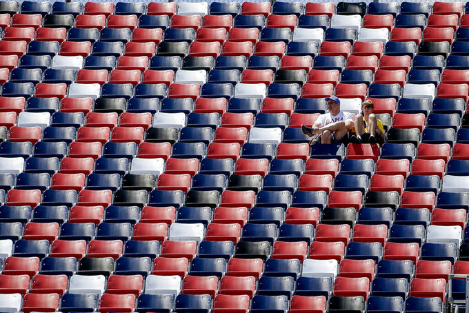 Two fans watch during the General Tire 200 ARCA Series auto race at Talladega Superspeedway, Saturday, April 24, 2021 in Talladega, Ala. (AP Photo/Butch Dill)
