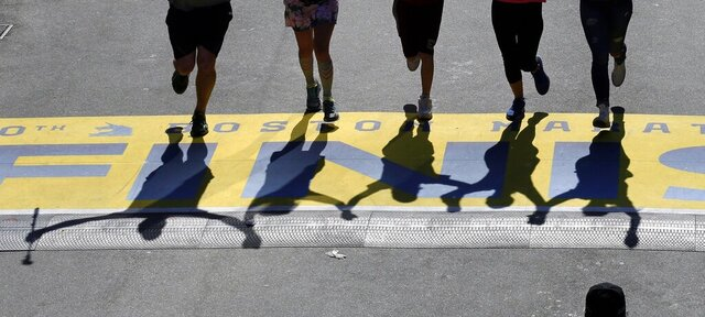 FILE - In this April 18, 2016, file photo, runners' shadows precede them across the finish line of the 120th Boston Marathon in Boston. Due to the COVID-19 virus pandemic, the 124th running of the Boston Marathon was postponed from its traditional third Monday in April to Monday, Sept. 14, 2020. (AP Photo/Charles Krupa, File)