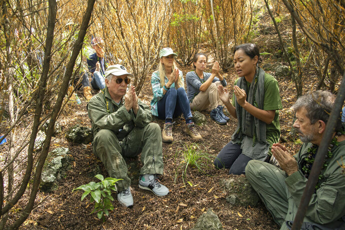 In this Friday, Aug. 16, 2019 photo, musician Paul Simon, left, joins in a prayer lead by Aimee Sato, second from right, prior to the planting of a lama tree at Auwahi Forest Reserve on Maui, Hawaii. The tree planting is a part of a growing forest restoration effort on Hawaii's second largest island. (Anna Kim/Honolulu Star-Advertiser via AP)