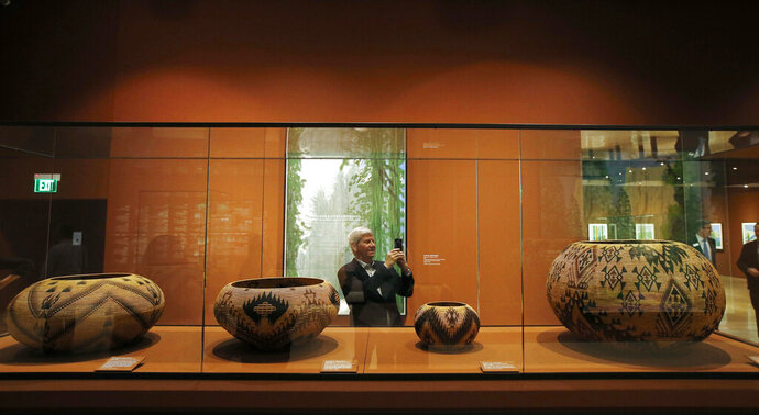 In this Wednesday, Oct. 23, 2019, photo, Richard Benefield, former executive director of the David Hockney Foundation, takes a photo inside the exhibit of Hockney's Yosemite artistic work, background, along with baskets from weavers from the Miwok and Mono Lake Paiute tribes on display at the Heard Museum in Phoenix.