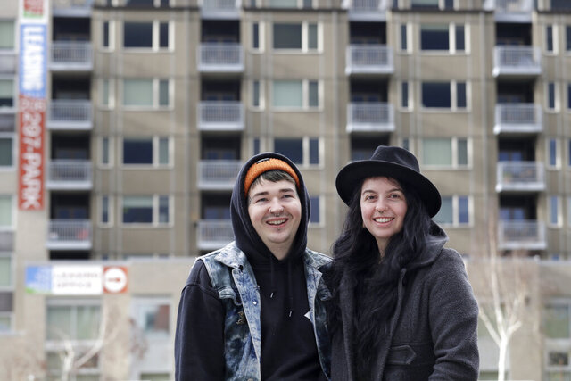 In this photo taken Monday, Nov. 25, 2019, Aspen Day-Flynn, right, a hair stylist, stands with her boyfriend Travis Tolin, a tattoo artist, in front of their apartment building in Seattle. The pair were considering a move back to her native Seattle this fall when their landlord in Phoenix helped seal their decision. Overnight, the monthly rent on their 986-square-foot two-bedroom, one-bath house jumped 50 percent, from $1,000 to $1,500 as the owner announced his plans for a major renovation. (AP Photo/Elaine Thompson)