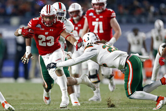 Wisconsin running back Jonathan Taylor (23) breaks a tackle attempt by Miami defensive back Sheldrick Redwine (22) during the first half of the Pinstripe Bowl NCAA college football game Thursday, Dec. 27, 2018, in New York. (AP Photo/Adam Hunger)