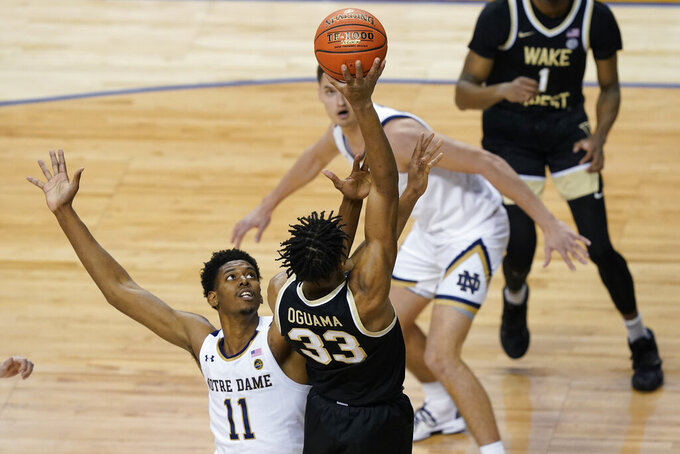 Wake Forest forward Ody Oguama (33) takes a shot as Notre Dame forward Juwan Durham (11) defends during the first half of an NCAA college basketball game in the first round of the Atlantic Coast Conference tournament in Greensboro, N.C., Tuesday, March 9, 2021. (AP Photo/Gerry Broome)