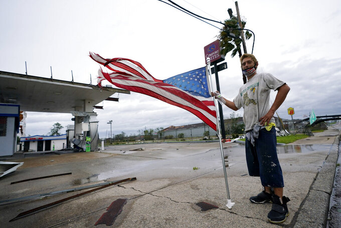 FILE - In this Aug. 27, 2020, file photo, Dustin Amos walks near debris at a gas station, in Lake Charles, La., after Hurricane Laura moved through the state. (AP Photo/Gerald Herbert, File)