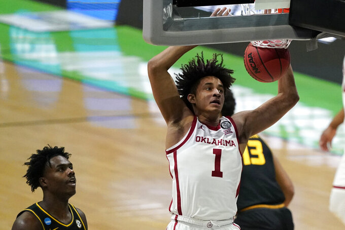 Oklahoma forward Jalen Hill (1) dunks the ball ahead of Missouri forward Kobe Brown, left, during the first half of a first-round game in the NCAA men's college basketball tournament at Lucas Oil Stadium, Saturday, March 20, 2021, in Indianapolis. (AP Photo/Darron Cummings)