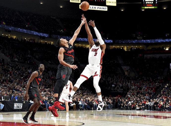 Miami Heat guard Dwyane Wade, right, hits a shot over Portland Trail Blazers guard CJ McCollum, center, as forward Al-Farouq Aminu watches during the first half of an NBA basketball game in Portland, Ore., Tuesday, Feb. 5, 2019. (AP Photo/Steve Dykes)