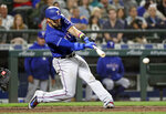 Texas Rangers' Robinson Chirinos singles in a run against the Seattle Mariners during the sixth inning of a baseball game Tuesday, May 15, 2018, in Seattle. (AP Photo/Elaine Thompson)