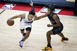 San Antonio Spurs' Tre Jones drives against Brooklyn Nets' David Duke Jr. during the second half of an NBA summer league basketball game Sunday, Aug. 15, 2021, in Las Vegas. (AP Photo/John Locher)