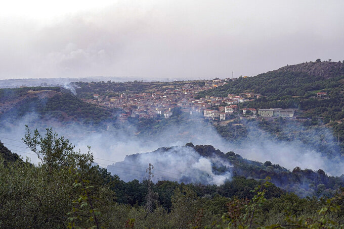 Flames are seen a wooded area near buildings, in Cugliari, near Oristano, on the island of Sardinia, Italy, Monday, July 26, 2021. Fires raged Sunday on Italy's Mediterranean island of Sardinia, where nearly 400 people were evacuated overnight. No deaths or injuries have been reported. Firefighters said several homes were damaged in the island's western interior region. (Alessandro Tocco/LaPresse via AP)