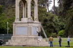 Workers from the Recreation and Parks Department paint over graffiti after a statue of Francis Scott Key was toppled from its pedestal in Golden Gate Park in San Francisco, Saturday, June 20, 2020. (Karl Mondon/Bay Area News Group via AP)
