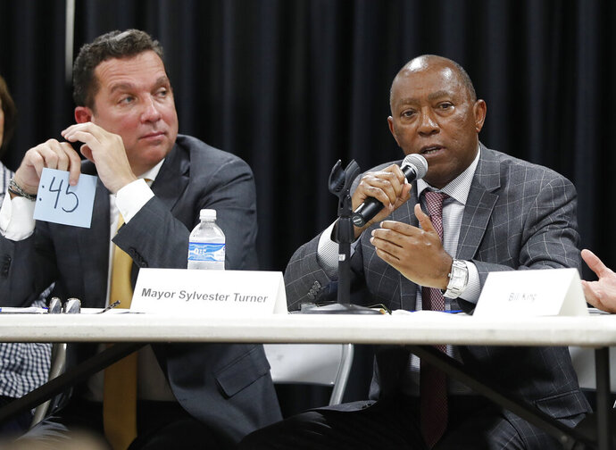 In this Sept. 2, 2019 photo, Mayor Sylvester Turner speaks as Tony Buzbee, left, listens during a mayoral candidate forum for the 2019 election in Houston.  As Turner seeks a second term, he's hoping to use residents' antipathy toward President Donald Trump to help him beat Turner, his biggest challenger. Crimes rates, allegations of City Hall corruption and the pace of the city's recovery after Hurricane Harvey are among the issues that have come up in the race. (Karen Warren/Houston Chronicle via AP)