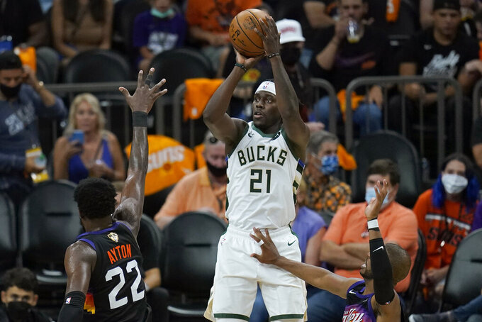 Milwaukee Bucks guard Jrue Holiday (21) shoots against the Phoenix Suns during the second half of Game 5 of basketball's NBA Finals, Saturday, July 17, 2021, in Phoenix. (AP Photo/Ross D. Franklin)