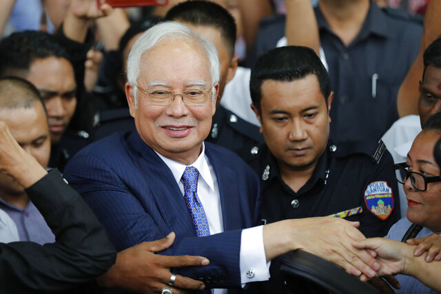 Former Malaysian Prime Minister Najib Razak, center, gets into a car after his court appearance at the Kuala Lumpur High Court in Kuala Lumpur, Malaysia, on April 3, 2019. Najib was found guilty Tuesday, July 28, 2020 in his first corruption trial linked to one of the world's biggest financial scandals - the billion-dollar looting of the 1MDB state investment fund. (AP Photo/Vincent Thian)