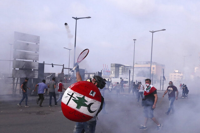 An anti-government protester throws back tear gas at riot policemen with a tennis racket during ongoing protests against the Lebanese government, in downtown Beirut, Lebanon, Saturday, June 6, 2020. Hundreds of Lebanese demonstrators gathered in central Beirut Saturday, hoping to reboot nationwide anti-government protests that began late last year amid an unprecedented economic and financial crisis. (AP Photo/Bilal Hussein)