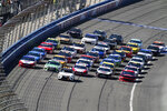 NASCAR Cup Series drivers line their cars up five wide in a salute to fans during pace laps for the NASCAR Cup Series auto race at Auto Club Speedway, in Fontana, Calif., Sunday, March 17, 2019. (AP Photo/Rachel Luna)