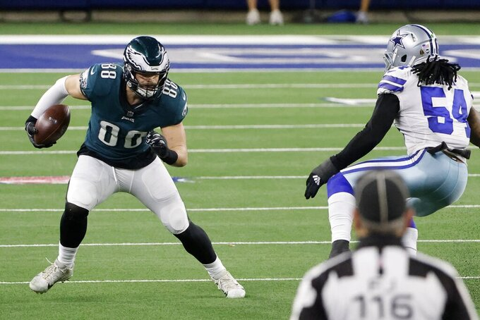 Philadelphia Eagles' Dallas Goedert (88) looks for running room after catching a pass as Dallas Cowboys linebacker Jaylon Smith (54) moves in to make the stop in the second half of an NFL football game in Arlington, Texas, Sunday, Dec. 27. 2020. Field Judge Mike Weatherford looks on at the play. (AP Photo/Michael Ainsworth)