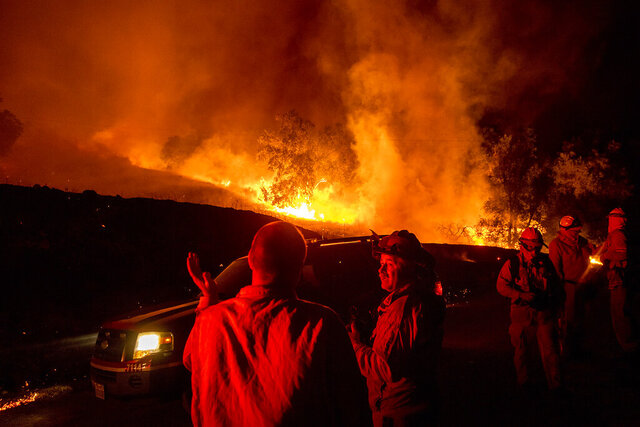 FILE - In this Oct. 24, 2019, file photo, firefighters confer while battling the Kincade Fire near Geyserville, Calif. Fire officials say Pacific Gas & Electric transmission lines sparked a wildfire last year in Northern California that destroyed hundreds of homes and led to the evacuation of nearly 100,000 people. The California Department of Forestry and Fire Protection issued the finding Thursday, July 16, 2020. (AP Photo/Noah Berger, File)
