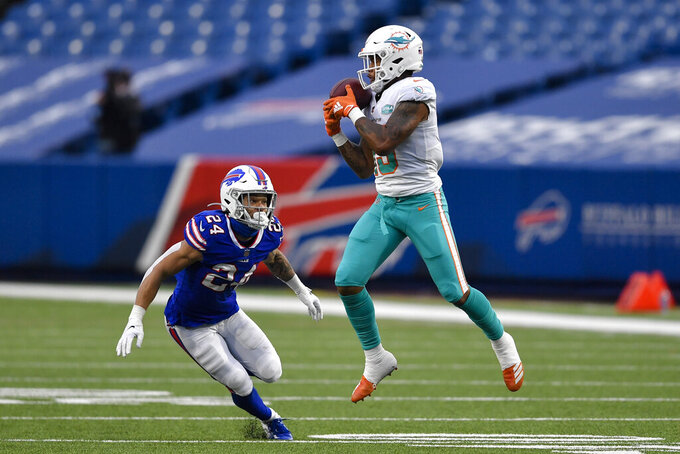 Miami Dolphins wide receiver Lynn Bowden (15) drops a pass against Buffalo Bills cornerback Taron Johnson (24) in the second half of an NFL football game, Sunday, Jan. 3, 2021, in Orchard Park, N.Y. (AP Photo/Adrian Kraus)