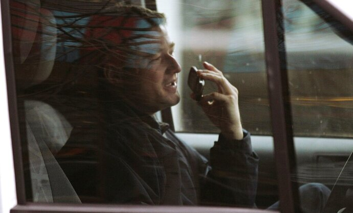 FILE - In this Dec. 14, 2011, file photo, a driver talks on a cell phone while driving through the Financial District of Boston. Massachusetts drivers would no longer be able to use hand-held cellphones behind the wheel under a bill approved in the House on Tuesday, Nov. 19, 2019, and coming up for a vote in the Senate on Wednesday before heading to Republican Gov. Charlie Baker's desk. (AP Photo/Charles Krupa, File)