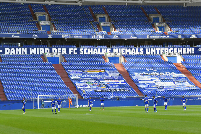 Schalke players get set before kickoff in the German Bundesliga soccer match between Hertha BSC Berlin and FC Schalke 04 in Gelsenkirchen, Germany, Wednesday, May 12, 2021. The banner in the background reads in German, Schalke will never go down. (AP Photo/Martin Meissner, Pool)