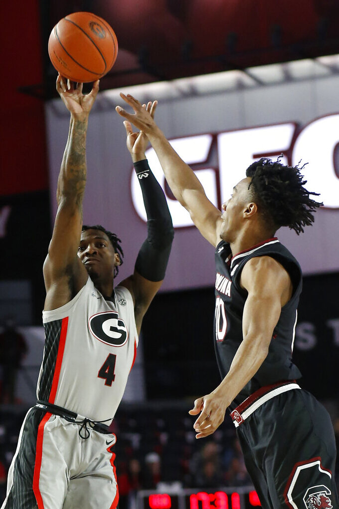 Georgia guard Tyree Crump (4) shoots while being defended by South Carolina forward Alanzo Frink (20) during an NCAA college basketball game  in Athens, Ga., on Saturday, Feb. 2, 2019.  (Joshua L. Jones/Athens Banner-Herald via AP)