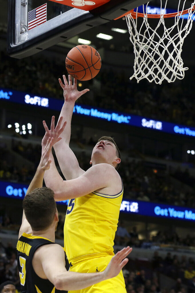 Michigan's Jon Teske (15) goes up for a shot over Iowa's Jordan Bohannon (3) during the first half of an NCAA college basketball game in the quarterfinals of the Big Ten Conference tournament, Friday, March 15, 2019, in Chicago. (AP Photo/Kiichiro Sato)