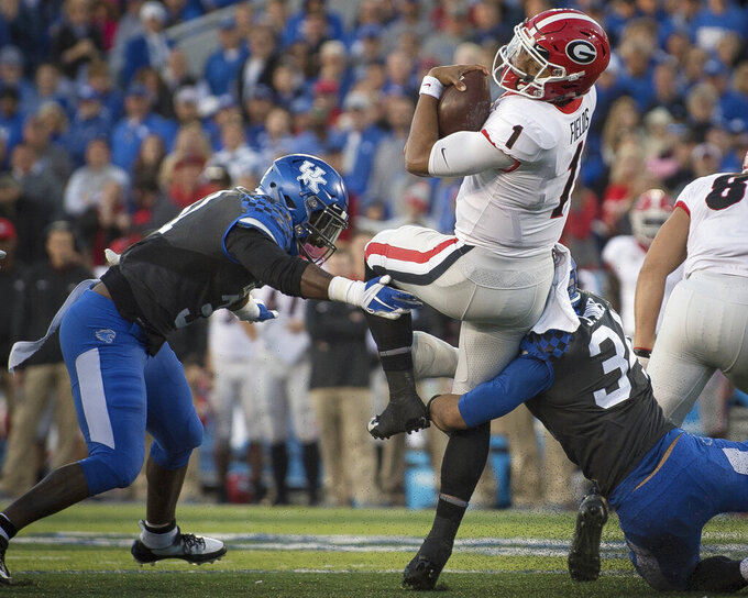 "FILE - In this Nov. 3, 2018, file photo, Georgia quarterback Justin Fields (1) is tackled by Kentucky linebacker Jordan Jones (34) and linebacker Jamar Watson (31) during the second half an NCAA college football game in Lexington, Ky. ""Of course, not having them, it's a difference,"" Watson said of his predecessors, who many of whom could be selected in the NFL draft. ""But that gives us a lot of confidence going into the season that coach (Mark) Stoops and the rest of defensive staff can groom us and take that step."" (AP Photo/Bryan Woolston, File)"