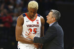 Virginia head coach Tony Bennett talks with forward Mamadi Diakite (25) after he fouled out during the second half of an NCAA college basketball game in Charlottesville, Va., Sunday, Dec. 8, 2019. Virginia defeated North Carolina 56-47. (AP Photo/Steve Helber)