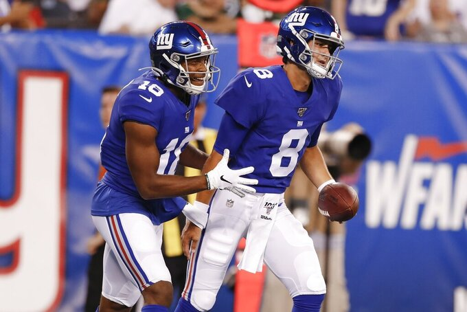 New York Giants quarterback Daniel Jones (8) celebrates with Bennie Fowler (18) after they connected for a touchdown during the first half of a preseason NFL football game against the New York Jets on Thursday, Aug. 8, 2019, in East Rutherford, N.J. (AP Photo/Michael Owens)