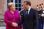 French President Emmanuel Macron welcomes German Chancellor Angela Merkel in the government building of Toulouse, southwestern France, Wednesday, Oct.16, 2019. President Emmanuel Macron and Chancellor Angela Merkel sought Wednesday to demonstrate the solidity of the French-German relationship at a meeting in southern France, one day before a key EU summit that may approve a divorce deal with Britain. (AP Photo/Frederic Scheiber)