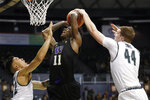 Hawaii's Dawson Carper (44) blocks a shot from Washington's Nahziah Carter (11) during the second half of an NCAA college basketball game Monday, Dec. 23, 2019, in Honolulu. (AP Photo/Marco Garcia)