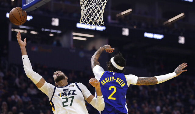 Utah Jazz center Rudy Gobert, left, reaches for a rebound past Golden State Warriors' Willie Cauley-Stein (2) in the first half of an NBA basketball game Wednesday, Jan. 22, 2020, in San Francisco. (AP Photo/Ben Margot)