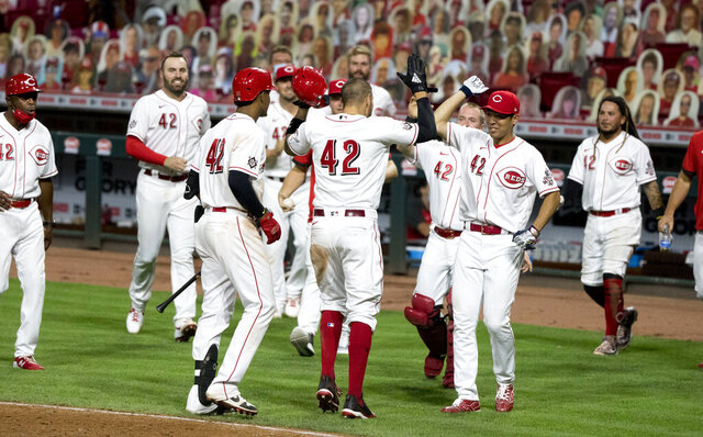 Cincinnati Reds' Nicholas Castellanos, center, celebrates with Shogo Akiyama, right, and other teammates after scoring the go-ahead game-ending run off a wild pitch from Chicago Cubs relief pitcher Craig Kimbrel in the seventh inning of the second baseball game of a doubleheader in Cincinnati, Saturday, Aug. 29, 2020. (Albert Cseare/The Cincinnati Enquirer via AP)