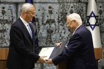 Israeli President Reuven Rivlin, right, hands a mandate to form new government to Blue and White Party leader Benny Gantz in Jerusalem, Wednesday, Oct. 23, 2019. (AP Photo/Sebastian Scheiner)