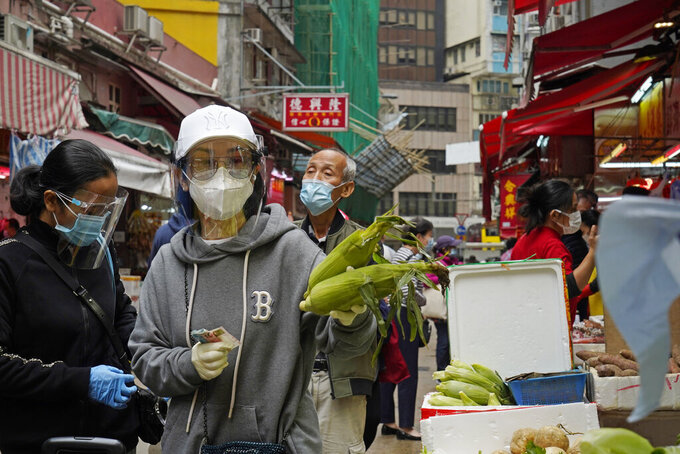 People wearing face masks to protect against the spread of the coronavirus shop at a local market in Hong Kong, Tuesday, Dec. 8, 2020. Hong Kong leader Carrie Lam said social distancing measures will be tightened as cases of the coronavirus continue to surge, with a ban on nighttime dining and more businesses ordered to close. (AP Photo/Kin Cheung)