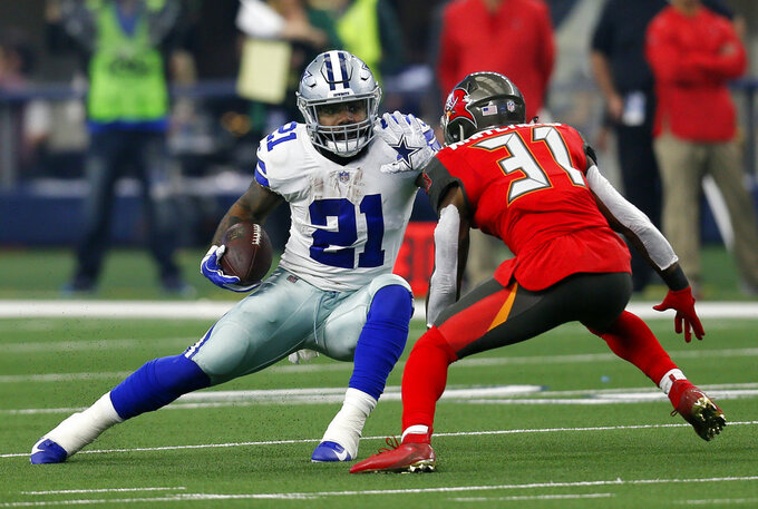 FILE - In this Sunday, Dec. 23, 2018 file photo, Dallas Cowboys running back Ezekiel Elliott (21) attempts to evade a tackle by Tampa Bay Buccaneers safety Jordan Whitehead (31) after Elliott caught a pass in the first half time of an NFL football game in Arlington, Texas. Ezekiel Elliott won his second NFL rushing title in three seasons for a Dallas offense that has been defined by the ground game for several years now. (AP Photo/Roger Steinman, File)