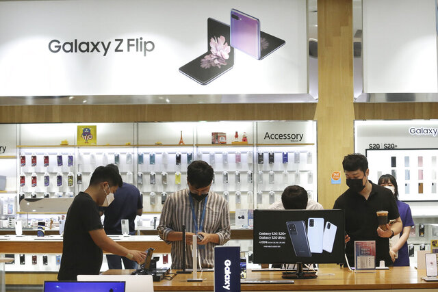 Visitors try out Samsung Electronics' Galaxy Z Flip smartphones at its shop in Seoul, South Korea, Tuesday, July 7, 2020. Samsung Electronics Co. said Tuesday its operating profit for the last quarter likely rose 23% from the same period last year, helped by robust demand for memory chips used in personal computers and servers as the coronavirus pandemic has more people working from home. (AP Photo/Ahn Young-joon)