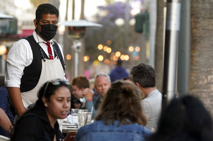 FILE - In this June 9, 2021, file photo, a server tends to customers in an outdoor dining area amid the COVID-19 pandemic on The Promenade, in Santa Monica, Calif. California regulators on Thursday, June 17, 2021, are set to approve revised worksite pandemic rules that allow fully vaccinated employees the same freedoms as when they are off the job. (AP Photo/Marcio Jose Sanchez, File)