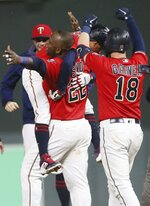 Minnesota Twins' Miguel Sano (22) carries Ronald Torreyes as Mitch Garver joins the celebration after Torreyes was hit by a pitch from Chicago White Sox's Jose Ruiz with the bases loaded for the winning run in the 12th inning of a baseball game Tuesday, Sept. 17, 2019, in Minneapolis. The Twins won 9-8. (AP Photo/Jim Mone)
