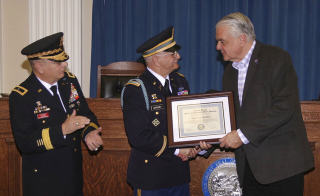 In this Dec. 11, 2019, photo, Army veteran Andrew LePeilbet, center, whose platoon came under heavy fire in Vietnam in 1969, receives a certificate from Gov. Steve Sisolak, right, for a Silver Star medal more than 50 years after he earned it while his brother retired Brig. Gen. Michael LePeilbet applauds, in Carson City, Nev. Andrew LePeilbet was honored for his courage and bravery in the battle near the Cambodian border. (Steve Ranson/Lahontan Valley News via AP)