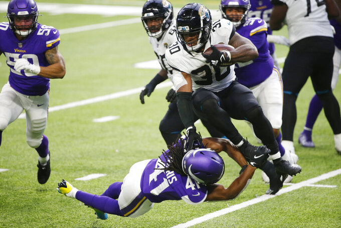 Jacksonville Jaguars running back James Robinson (30) is tackled by Minnesota Vikings safety Anthony Harris (41) during the second half of an NFL football game, Sunday, Dec. 6, 2020, in Minneapolis. (AP Photo/Bruce Kluckhohn)