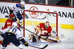 St. Louis Blues' Oskar Sundqvist (70) and Ivan Barbashev (49) look on as Calgary Flames goalie David Rittich stops a shot during the third period of an NHL hockey game in Calgary, Saturday, Nov. 9, 2019. (Jeff McIntosh/The Canadian Press via AP)